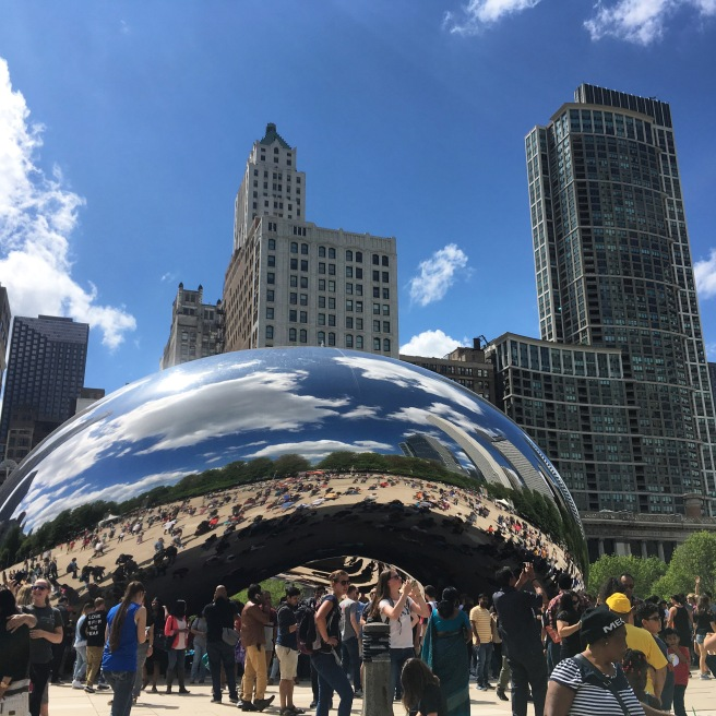 A view of 'the Bean,' formally known as Cloud Gate, a mirrored sculpture in the shape of a bean in Chicago's Millennium Park. In the sculpture you can see buildings reflections, and also behind it are more buildings. There is a crowd of people in front of the sculpture.