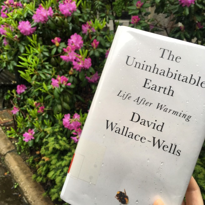 The cover of The Uninhabitable Earth, which is white with black text. At the bottom there is an image of a dead bumblebee. Behind the book you can see pink flowers and green leaves on a bush.