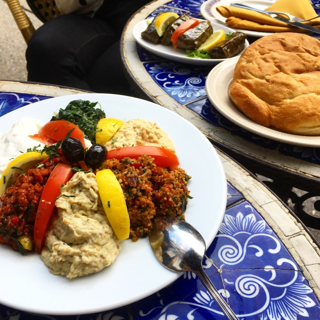 A mezze platter with dips such as hummus, baba ganoush, spinach, and yogurt on a blue tiled table, on the next table there is a loaf of bread and a dish with some stuffed grape leaves.