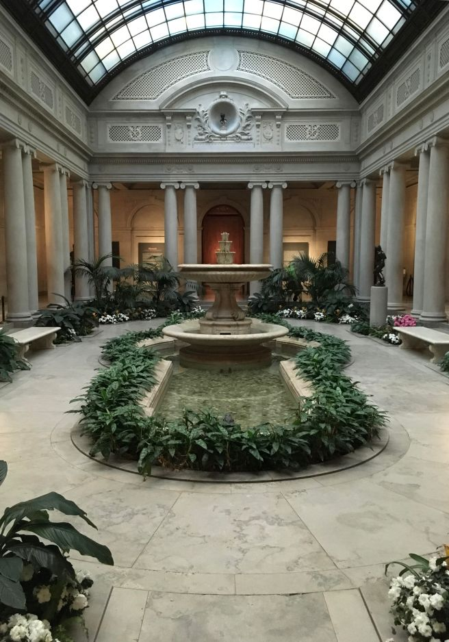 The Frick Collection's courtyard. There are columns around the perimeter, and plants and marble benches along the outside. In the center is a decorative fountain lined by green leafy plants.