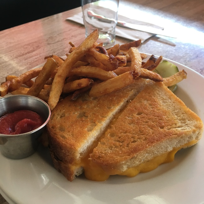 A grilled cheese sandwich on a white plate on a wooden table. There are also french fries and a little dish of ketchup on the plate.