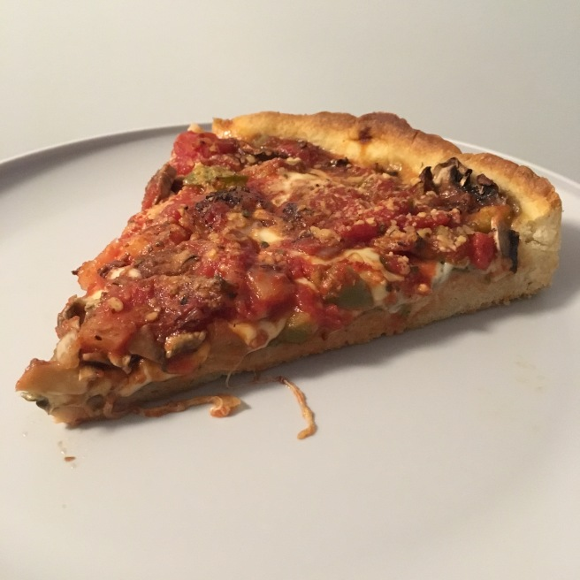 A slice of deep dish Chicago style pizza on a white plate.