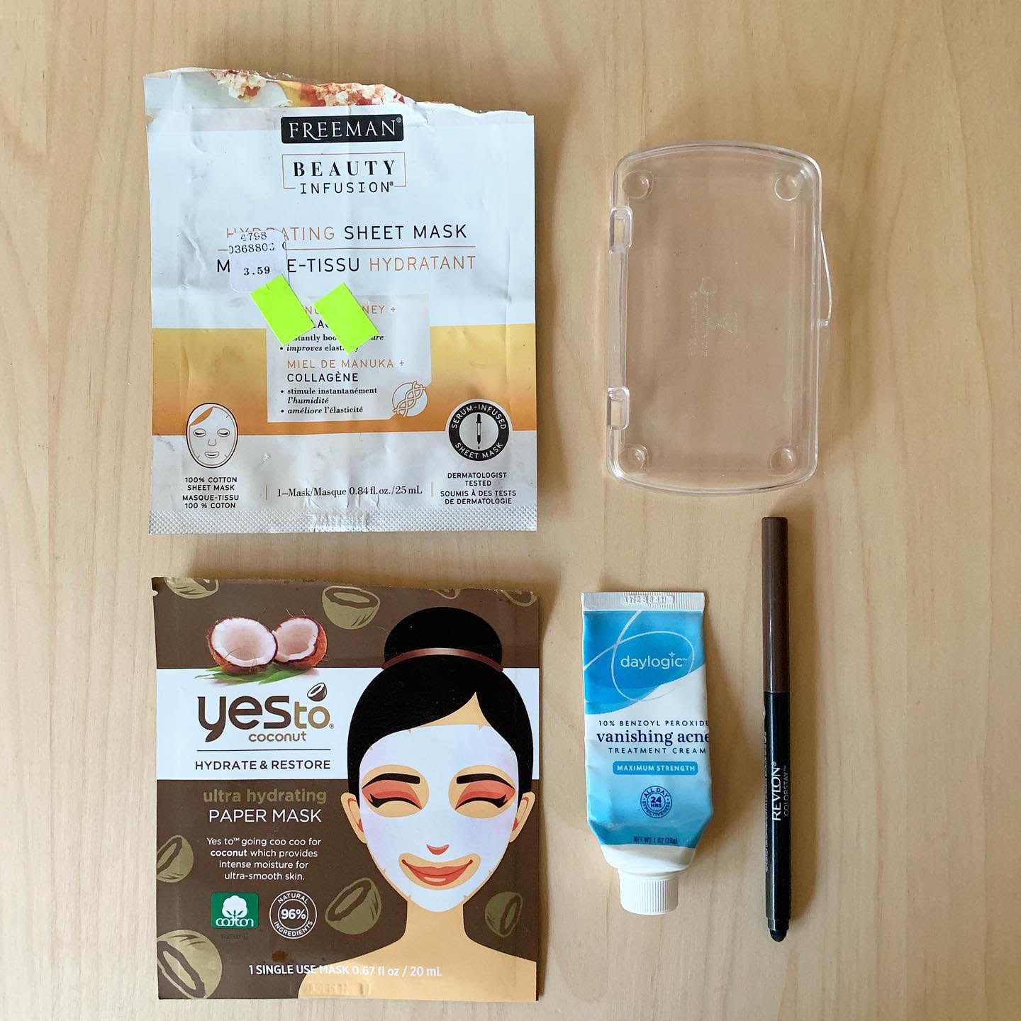 A photograph of empty beauty products - two face masks, a skincare product, an eyeliner, and a plastic box (representing a bar of soap).