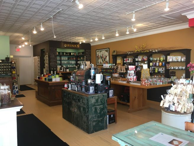 """A look into Verdigris shop. There are tables and counters with different items for sale such as teacups, mugs, chocolates in bags. In the back there is another counter with a sign that says """"Drinks"""" over it."""