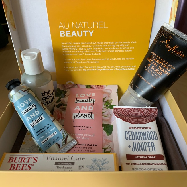 A box filled with 'natural' beauty products: facial wash/scrub, a small bar of soap, a hair mask packet, hand lotion, a mini toothpaste, and leave in conditioner.