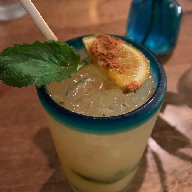 A yellow cocktail in a blue rimmed glass with a mint leaf and lemon with chili powder on top at El Kallejon.