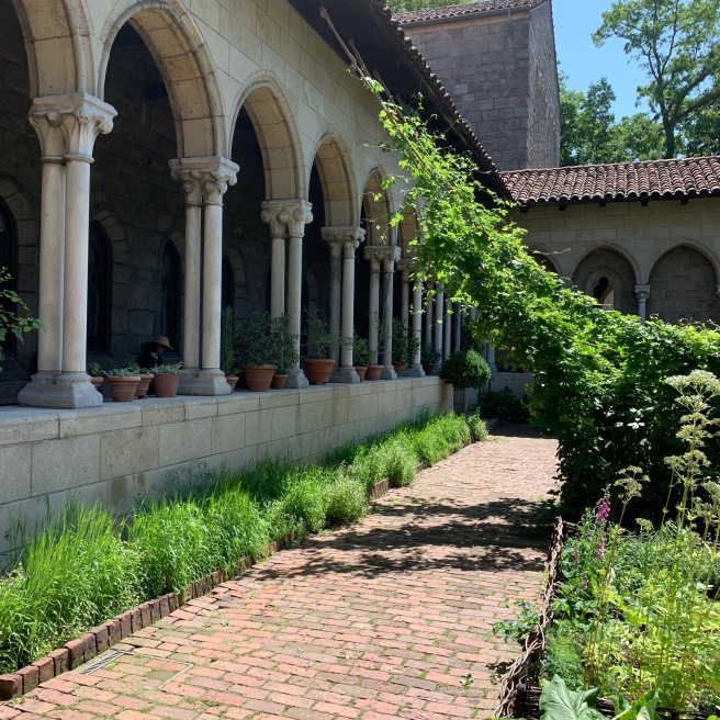 A walkway in the medieval garden at the Cloisters with decorative columns lining the building.