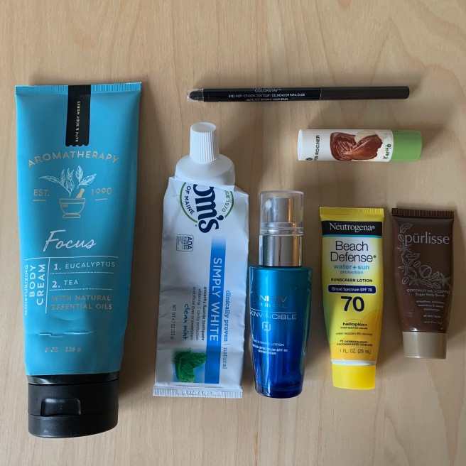 A photo of empty products that I used up in June: a full size lotion, two small sunblocks, a tube of toothpaste, an eyeliner, a lip balm, and a sample body scrub.
